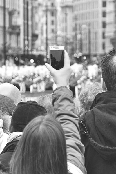 crowd filming video with smartphone